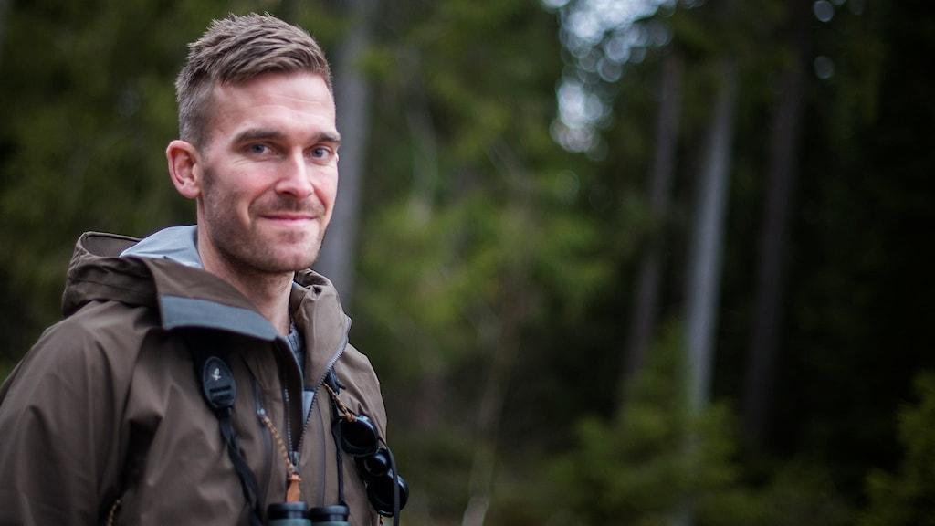 En man med en kikare står vid en skog