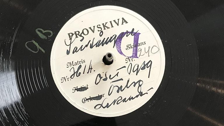 Närbild på en gammal så kalla lackskiva med handskriven etikett.