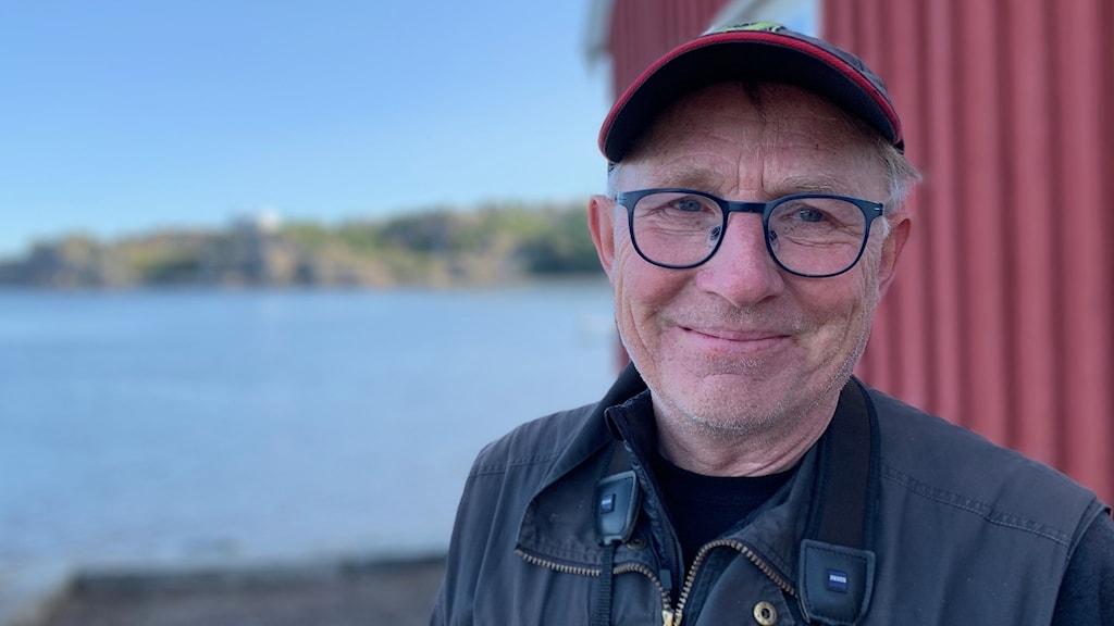 Man med keps och glasögon står vid Byfjorden.