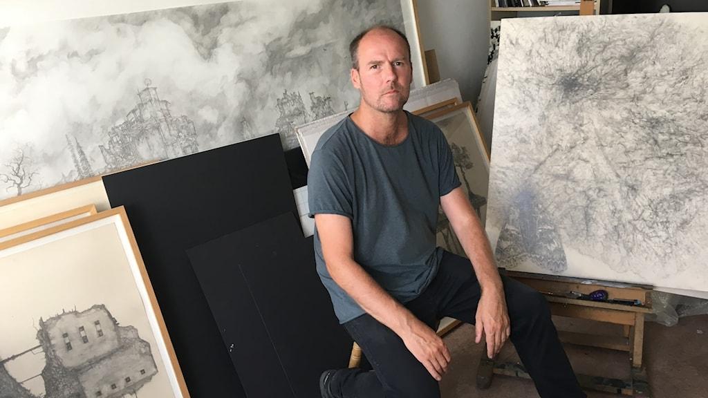 Mattias Bäcklin sitter framför några av sina verk i sin studio.