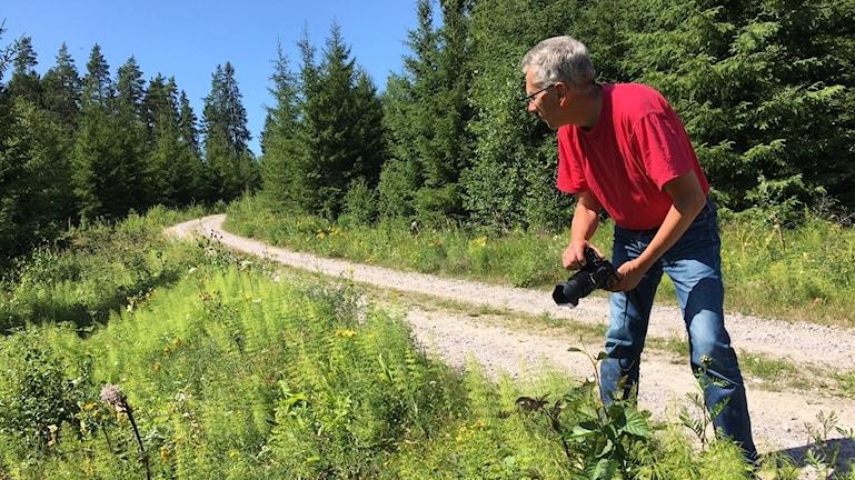 En man går med en kamera i handen på en grusväg.