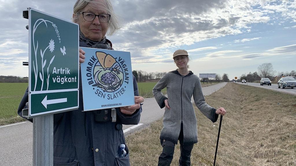 två kvinnor med skyltar där det står artrik vägkant och blomrik vägkant