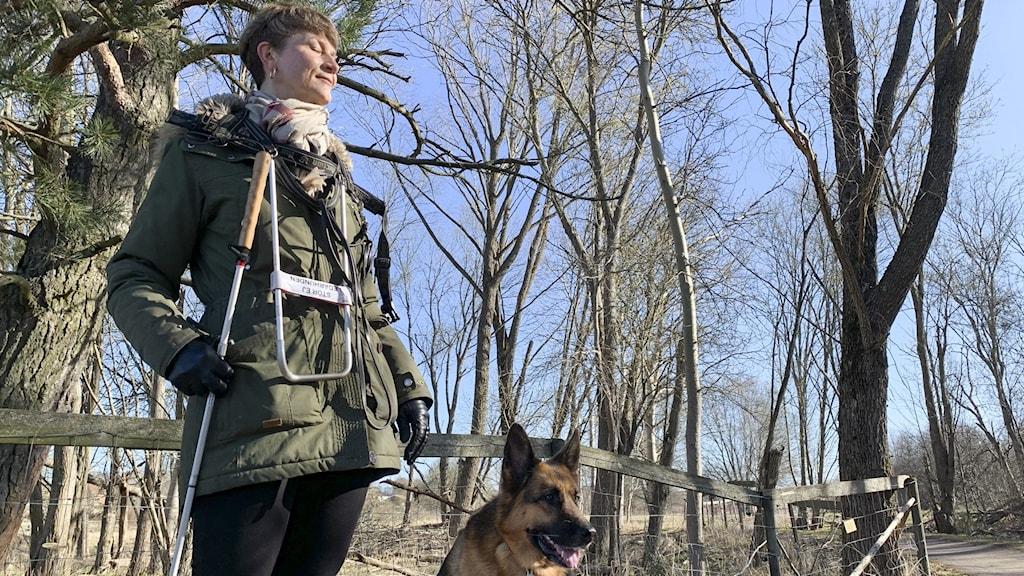 En kvinna står ute i solskenet och lyssnar med slutna ögon med en schäferhund intill sig.
