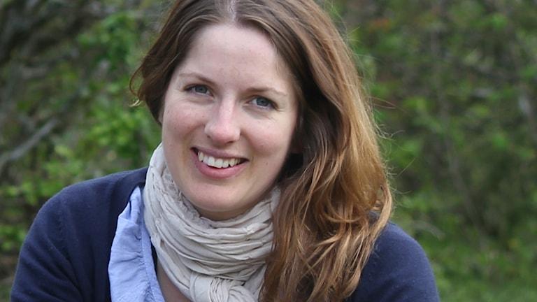 Porträttbild av leende kvinna utomhus med grönska i bakgrunden