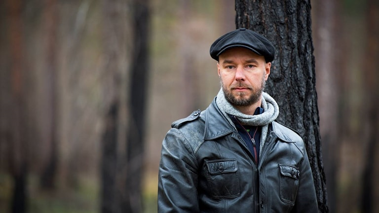 Porträttbild på man i sotig, bränd skog