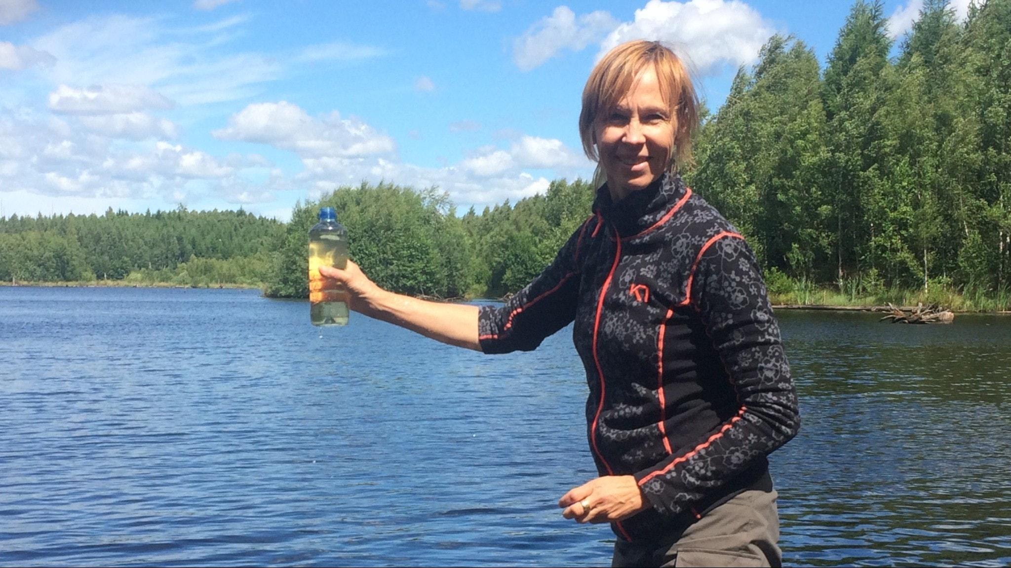 Kvinna med provflaska vid sjö
