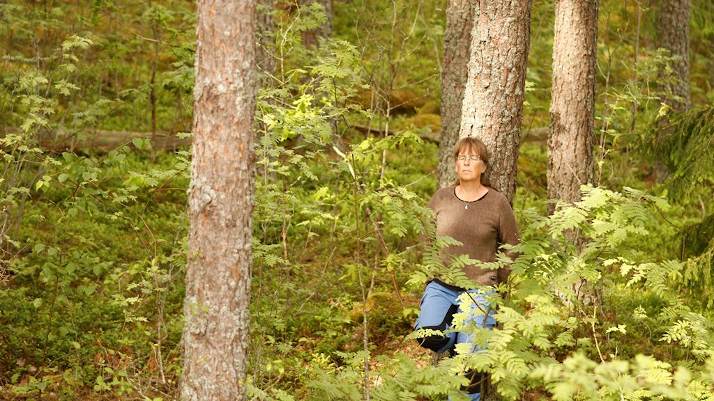 En kvinna står avslappnat lutad mot en trädstam i skogen med slutna ögon