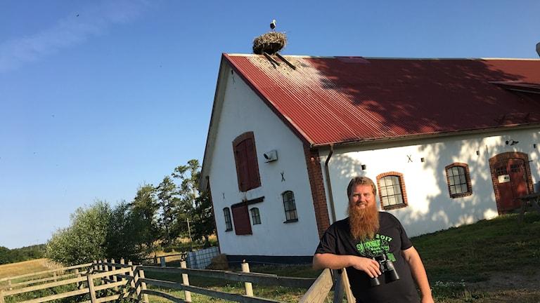 En skäggig ung man framför en skånsk bondgård med ett storkbo på taket