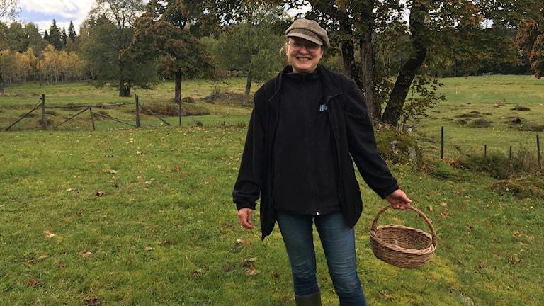 En kvinna med en svampkorg i en ängsmark.