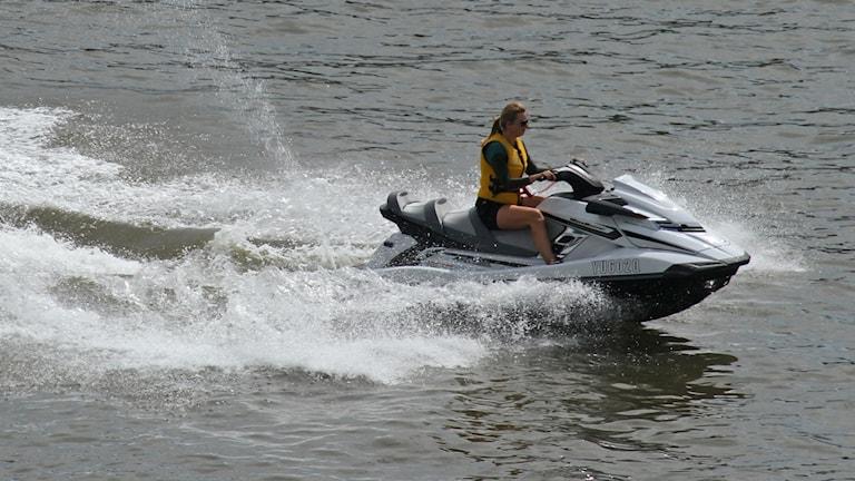 En vattenskoter (ett slags korsning mellan motorcykel och båt) forsar fram över vattenyta