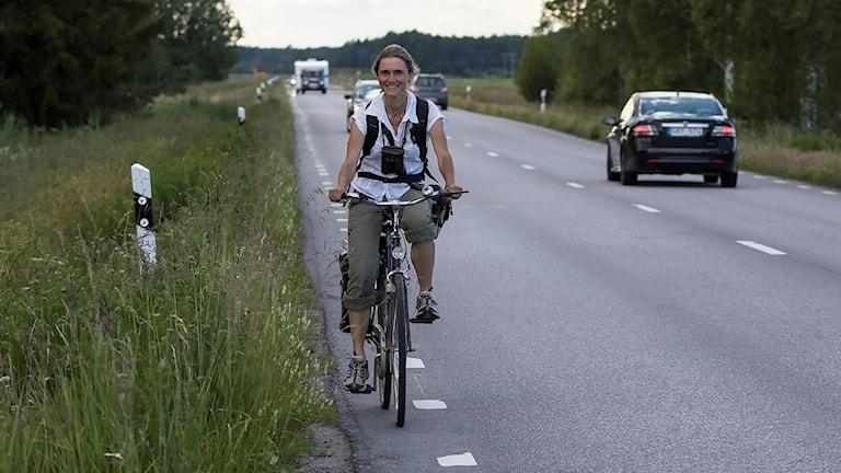 En kvinna på cykel på en landsväg. Hon tittar in i kameran och ler.