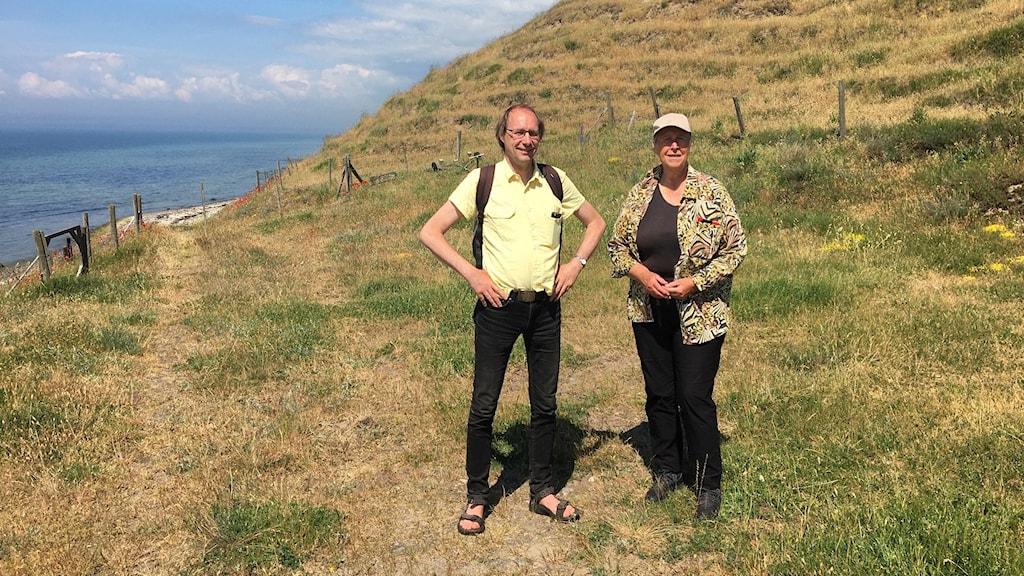 Ulf Ryde och Kerstin Svensson står på en torr betesmark vid havet.