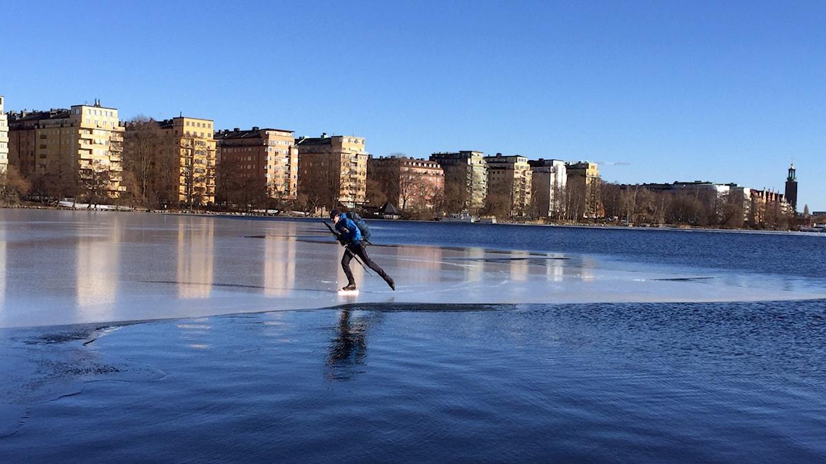 Mårten Ajne, skridskoåkare och författare, på Riddarfjärdens is mitt i Stockholm. Stadshuset längst bort till höger.