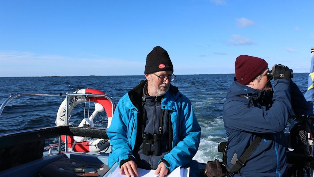 två personoer med kikare i en båt