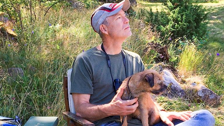 En man med kikare runt halsen, en hund i knäet och ett bord med floror och andra artbestämningsböcker.