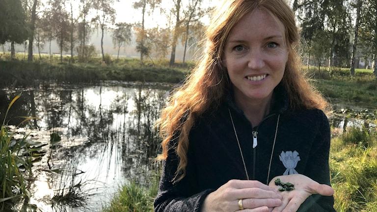 Sofie Olofsson vid en damm med en mossa i handen