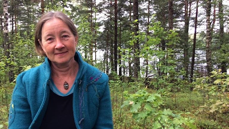 Porträttbild på kvinna i skog med sjö i bakgrunden