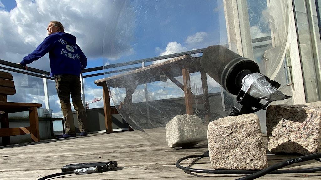 En man står vid ett balkongräcke och spanar ut mot himlen. I förgrunden syns en mikrofon med en skålformad parabol.