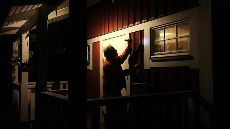 En man på en veranda lyser med ficklampa på den faluröda ytterväggen.