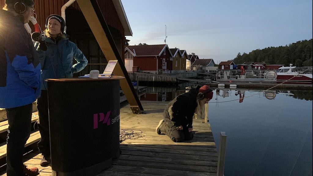 En man intervjuas av kvinna på en brygga. Bredvid sitter en annan kvinna och tittar ner i vattnet.