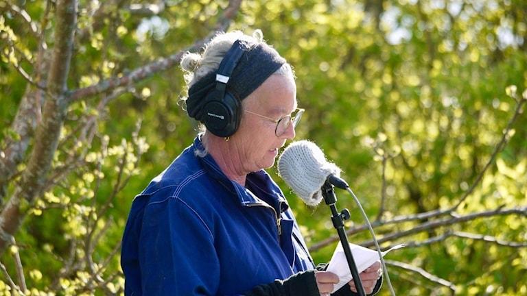 Kvinna med hörlurar vid mikrofon. Försommargrönska i bakgrunden.
