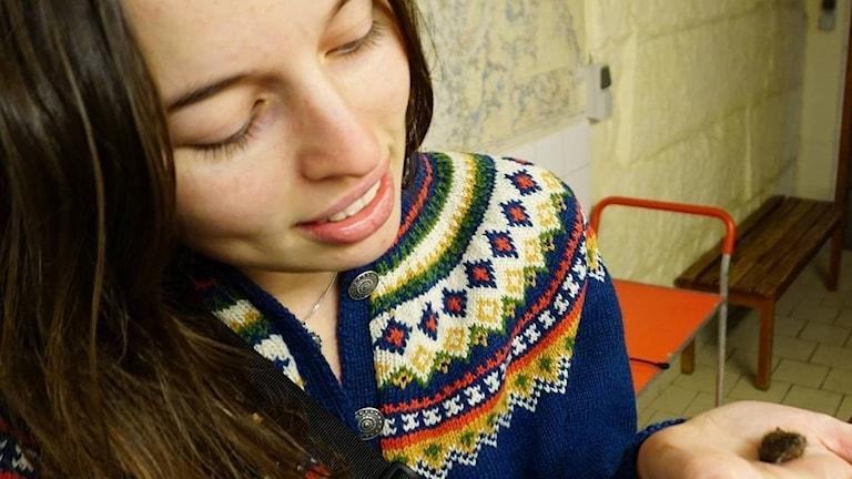 En ung kvinna tittar på något litet och borstigt som ligger i hennes handflata.