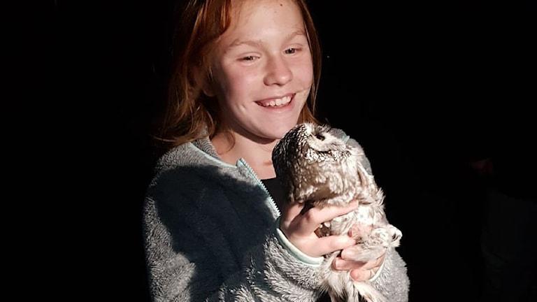 En elvaårig flicka med en pärluggla i famnen.