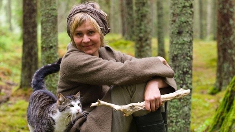 En kvinna sitter i skogen i sällskap med en katt