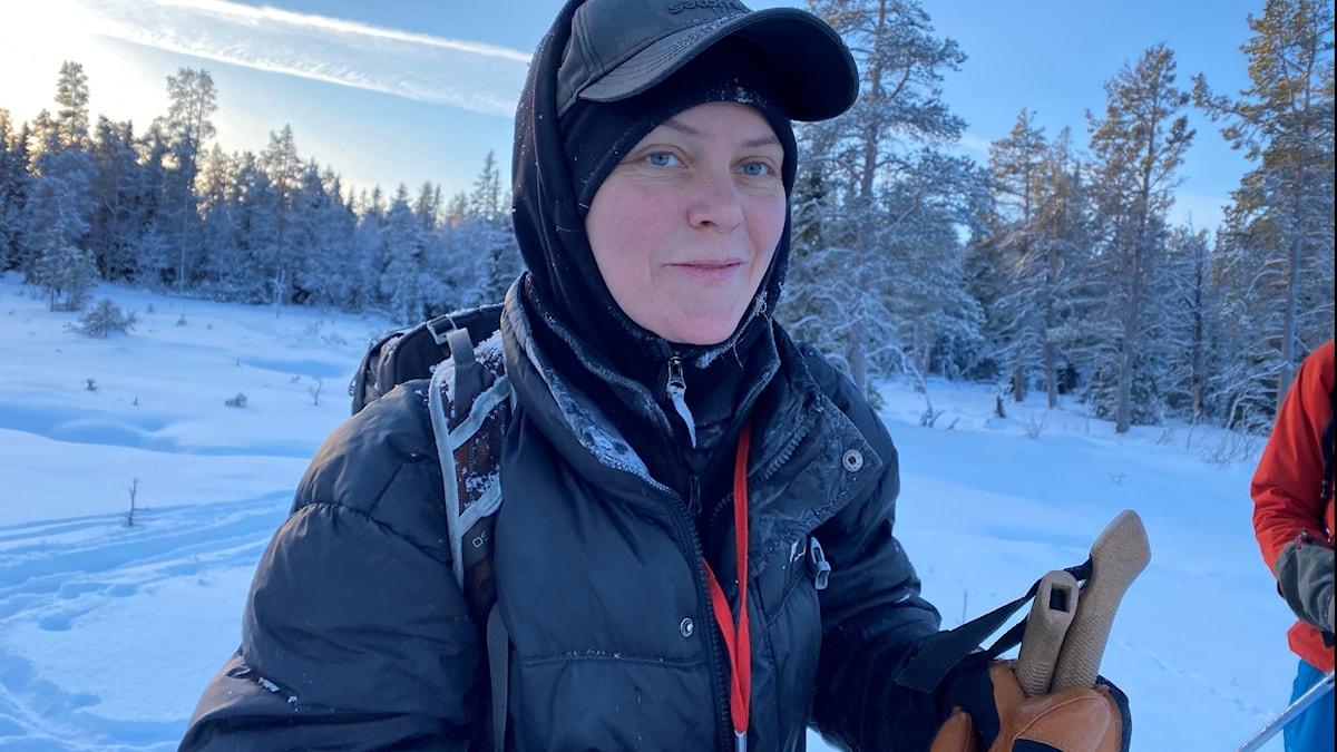 Kvinna med vinterkläder i snölandskap, på skidor