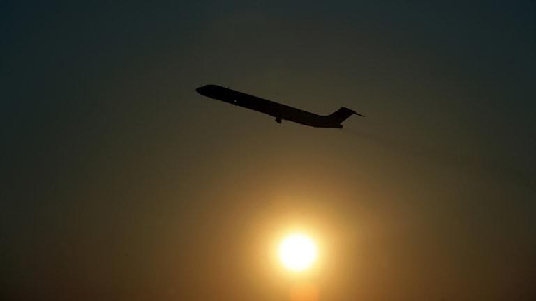 Flyg lyfter med solen i bakgrunden