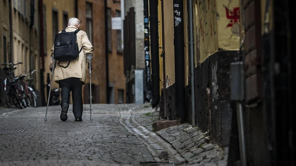 En äldre kvinna tar sig fram i Gamla stan med hjälp av kryckor