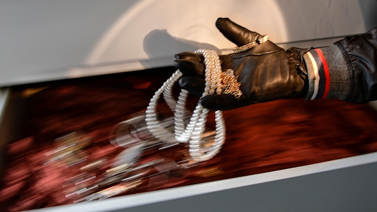 Hand iklädd handske tar smycken ur en låda.
