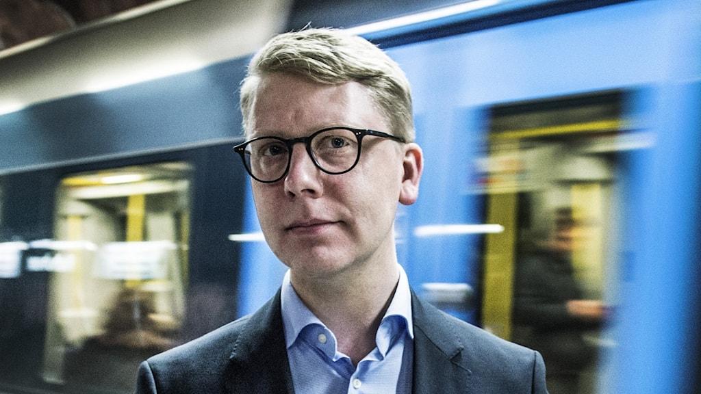 Trafikregionråd Kristoffer Tamsons står på perrongen framför ett tunnelbanetåg i rörelse.