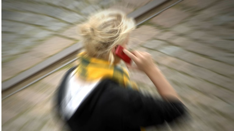 Kvinna talar i sin mobiltelefon. Foto: Hasse Holmberg/Scanpix