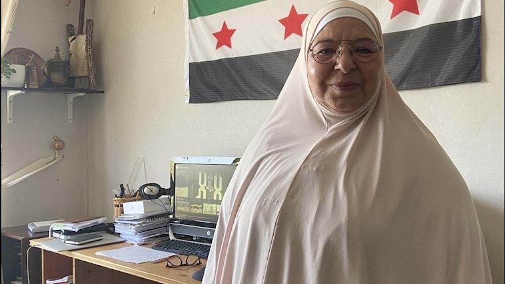 Fahyma står i en vit slöja och har läsglasögon på sig. Hon ler och tittar in i kameran. Bakom henne står en dator på ett skrivbord och papper och dylikt på.