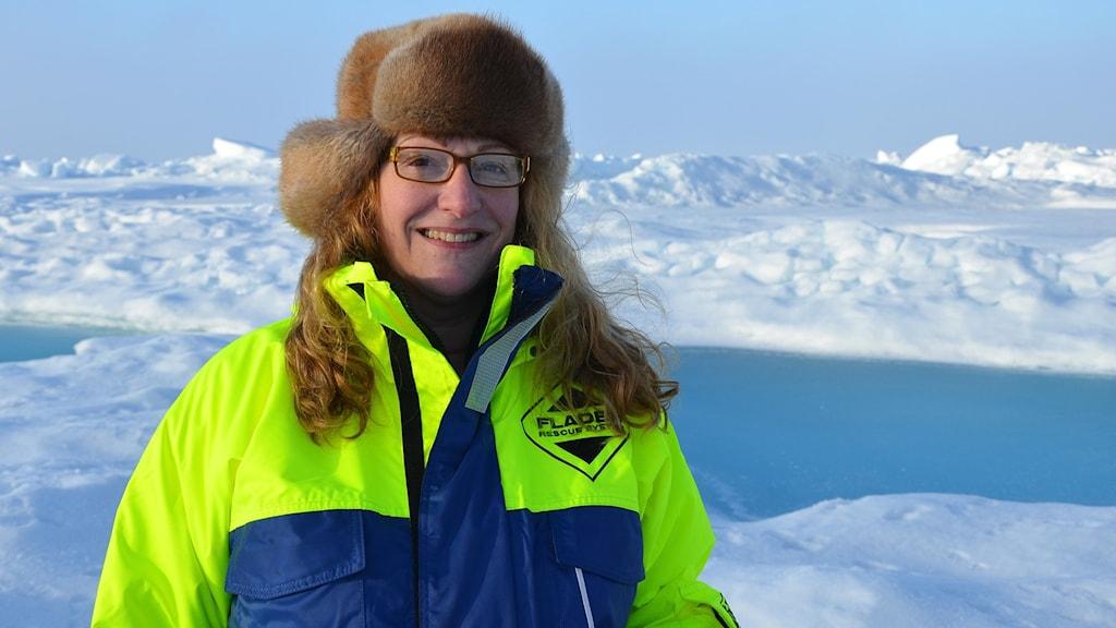 Kvinna med långt hår och glasögon och iförd pälsmössa och grönblå vinterjacka står framför snötäckt slätt.