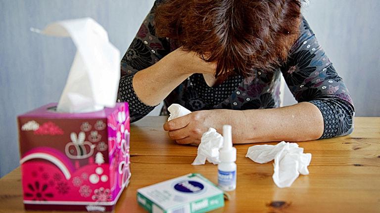 En förkyld kvinna sitter vid ett bord omgiven av näsdukar, nezeril och febernedsättande tabletter Foto: Jessica Gow / Scanpix.