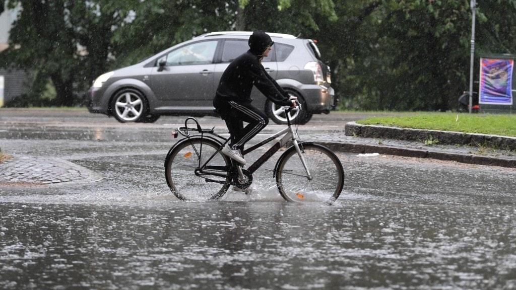Vattenfylld gata med en cyklist och en bil.
