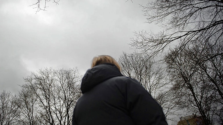 Kvinna i dunjacka står med ryggen till. Foto: Scanpix