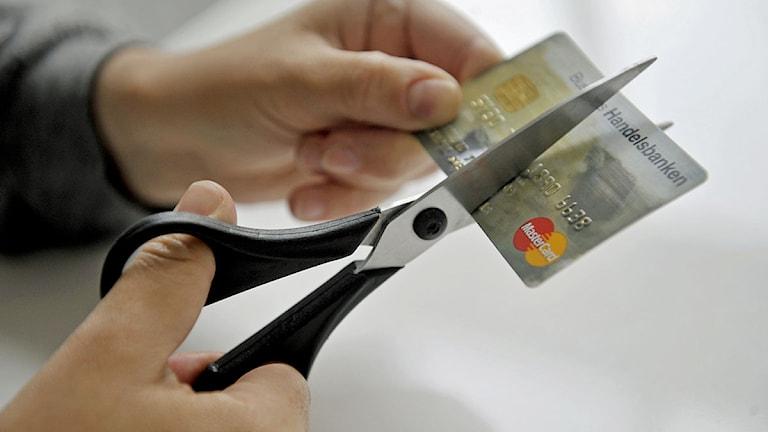 Person klipper sönder kontokort. Foto: Jessica Gow /Scanpix