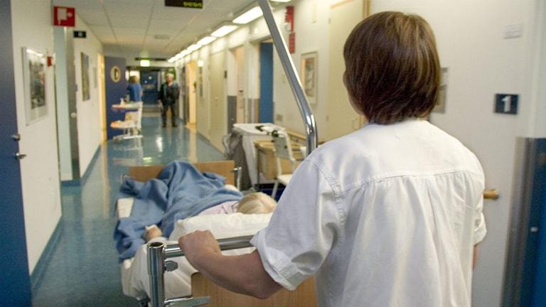 Sjukvårdspersonal rullar sängliggande patient genom korridoren, ortopedkliniken S:t Görans sjukhus.