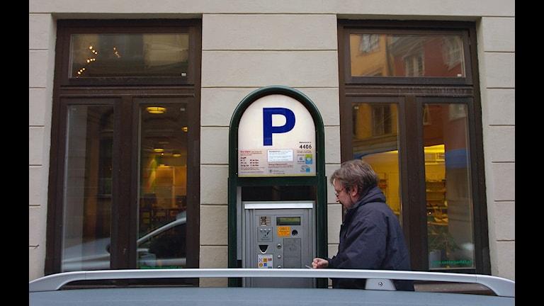Parkeringsautomat mot husvägg i Stadsmiljö. Man som betalar för sin bil som står på gatan.