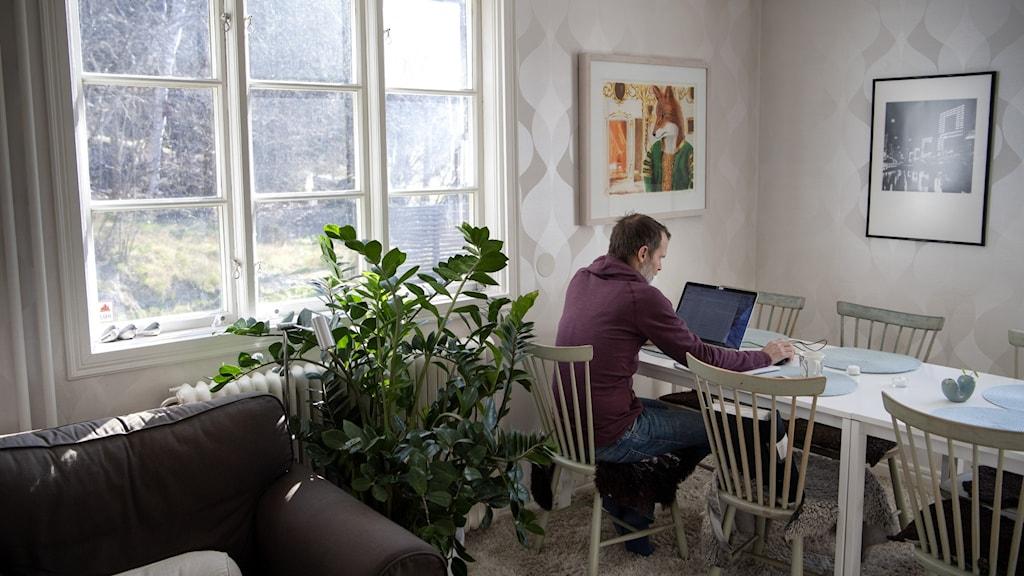 Man med bärbar dator jobbar hemifrån.