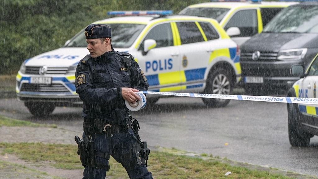 Polis drar ett avspärrningsband. I bakgrunden polisbilar.
