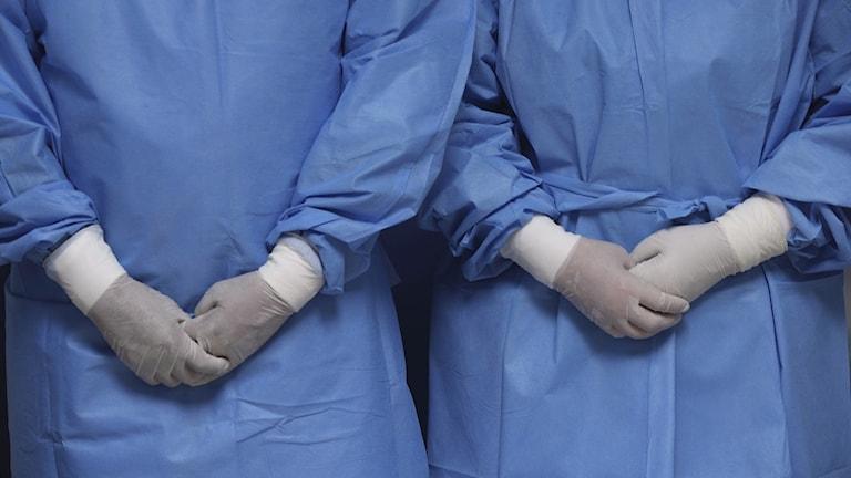Två sjukvårdare står med händerna i kors iklädd smittskyddsdräkter