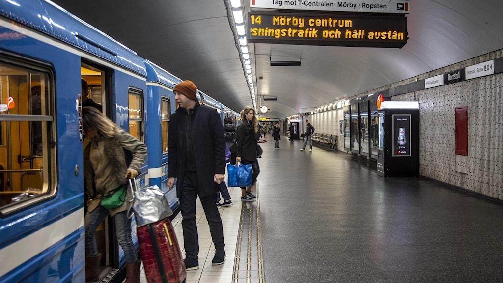 Gammaltunnelbanevagn med öppna dörrar och resenärer. Skylten visar att tåget ska åka mot Mörby centrum