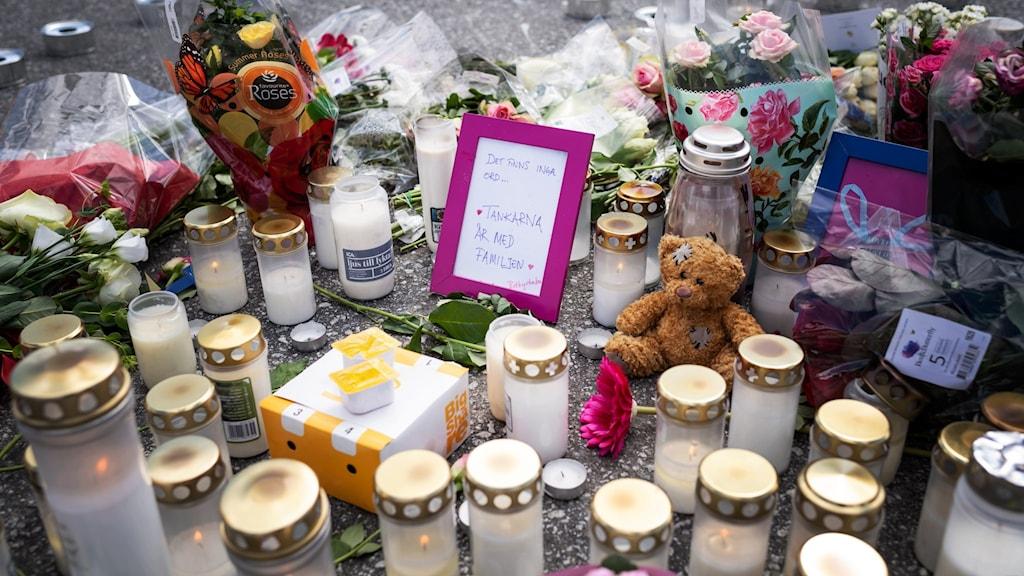 Blommor och ljus på platsen där en tolvårig flicka sköts ihjäl vid en bensinmack i Hallunda i Botkyrka, söder om Stockholm