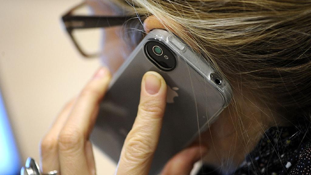 Kvinna talar i mobiltelefon.