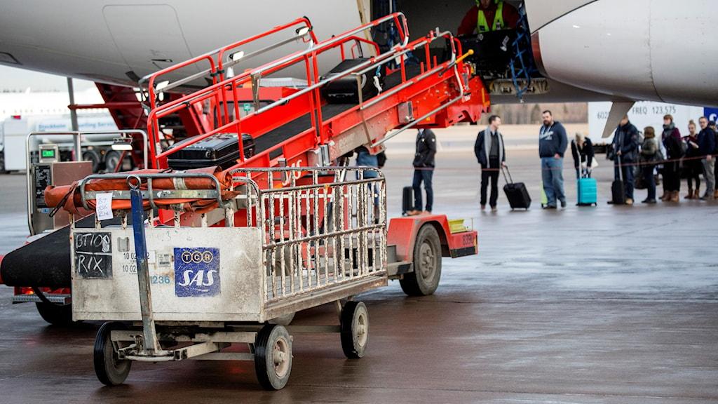 En bagagevagn och ett bagageband utanför ett flygplan på Stockholm Arlanda Airport.