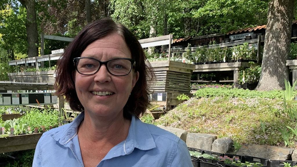 Kvinna i blå skjorta står bland växter utomhus.